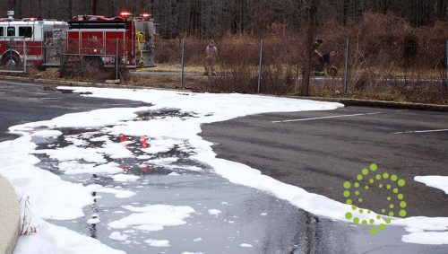 Firefighting Foam, which commonly includes PFAS compounds, on a road with firetruck and fire fighters in background